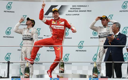 Der viermalige Champion Sebastian Vettel springt vor Glück auf dem Podium in Malaysia. Die Mercedes-Piloten dagegen wirken bedröppelt.