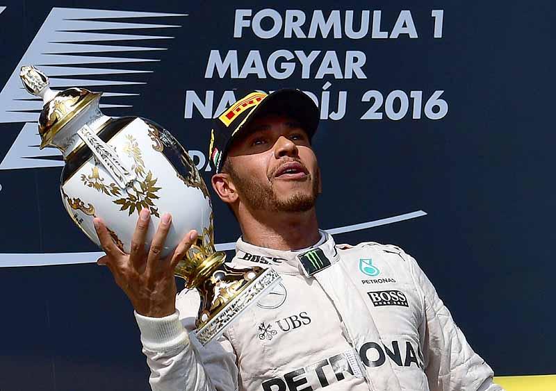 Lewis Hamilton präsentiert die Siegertrophäe auf dem Podium.