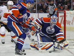 Edmontons Goalie Devan Dubnyk schnappt sich den Puck, Verteidiger Nick Schultz schirmt gegen die Calgary Flames gekonnt ab.
