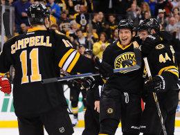 """""""Manchmal hast du einfach Glück"""": Vorlagen-König Dennis Seidenberg (re.) bejubelt einen Bruins-Treffer mit Gregory Campbell (#11) und Andrew Ference (#21)."""