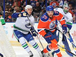 Kanadisches Duell hinterm Tor: Leon Draisaitl (in Orange) gegen Nikita Tryamkin von den Canucks.