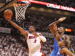 Durchsetzungsstark: Miamis Wade zieht gegen Oklahomas Ibaka und Westbrook zum Korb.