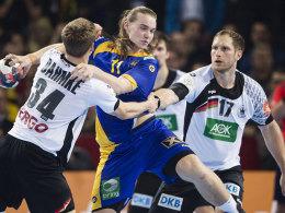 Die Kieler Rune Dahmke und Steffen Weinhold nehmen Lukas Nilsson in die Zange.