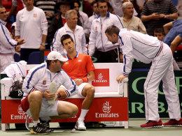 Novak Djokovic wird während seines Davis-Cup-Matches gegen Sam Querrey am rechten Fuß behandelt