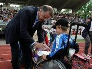 Ottmar Hitzfeld gibt einem Fan im Rollstuhl ein Autogramm
